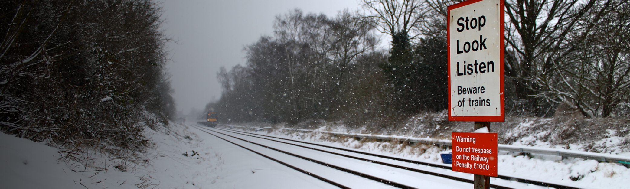 Railway level crossing with signs and train in the distance in the snow